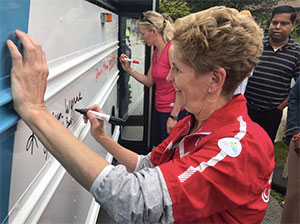Hon. Catherine McKenna, Canada's Minister of Environment and Climate Change and Premier of Ontario Kathleen Wynne signing our Canada 150 Rouge Park Express bus in June 2017